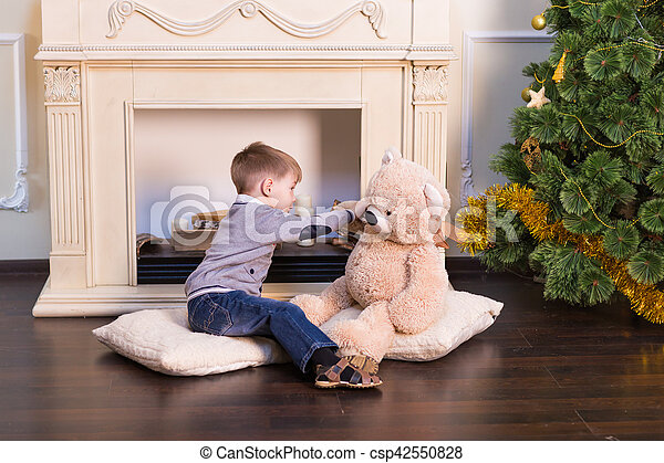 Child boy playing with soft toy bear under the Christmas tree. - csp42550828