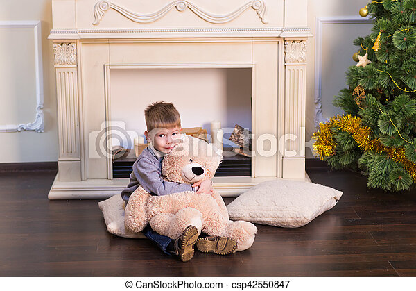 Child boy playing with soft toy bear under the Christmas tree. - csp42550847