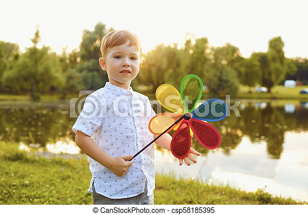 Child boy with toy in hand at sunset in park. - csp58185395