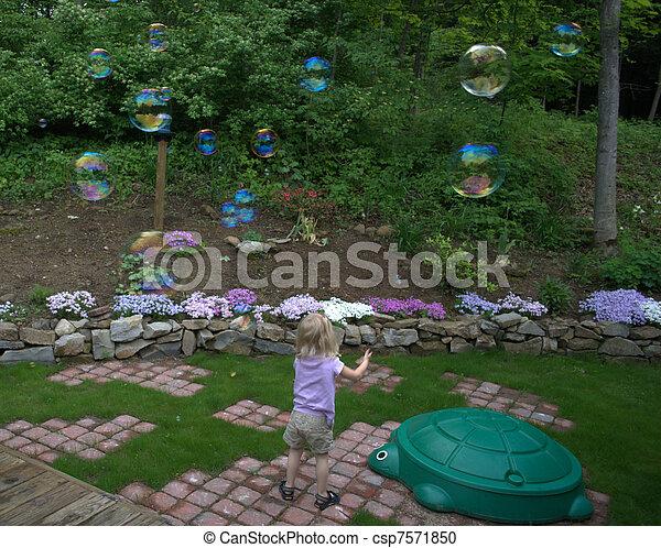Child Chasing Bubbles - csp7571850