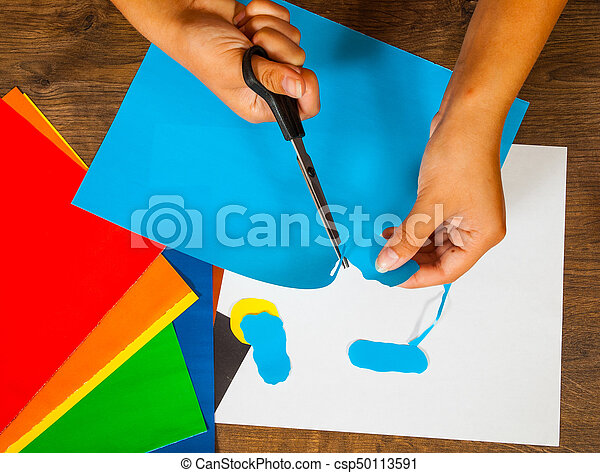 Child cuts out of paper. Sheets of colored paper. Kids art. Crafts concept. Handmade. on wooden table top view.