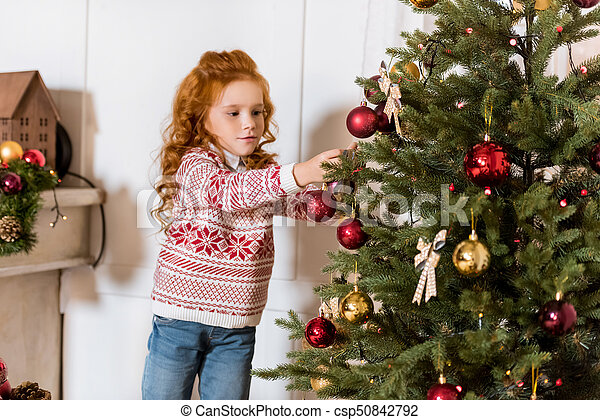 little girl decorating christmas tree with toys at home