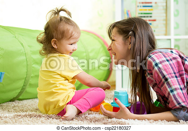 child girl and her mother playing together with toys - csp22180327