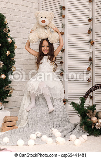 child girl playing with teddy bear near the Christmas tree - csp63441481