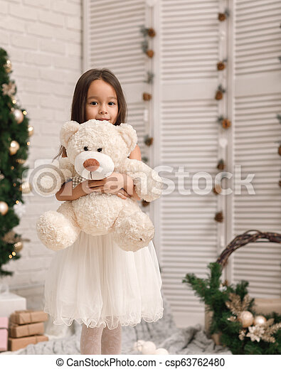child girl playing with teddy bear near the Christmas tree - csp63762480