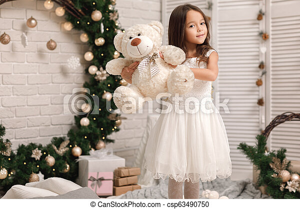 child girl playing with teddy bear near the Christmas tree - csp63490750