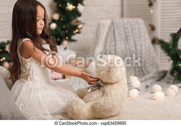 child girl playing with teddy bear near the Christmas tree - csp63429895