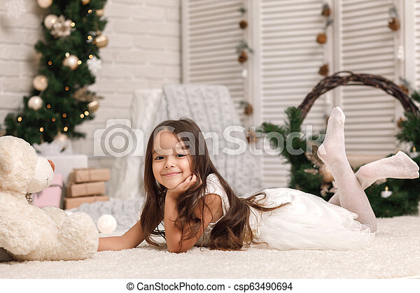child girl playing with teddy bear near the Christmas tree - csp63490694