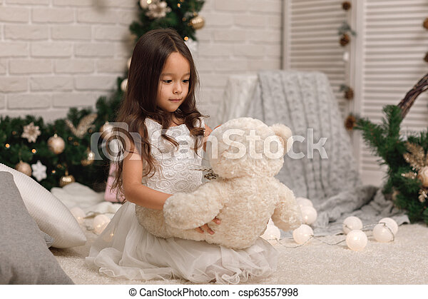 child girl playing with teddy bear near the Christmas tree - csp63557998