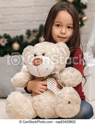 child girl playing with teddy bear near the Christmas tree - csp63429802