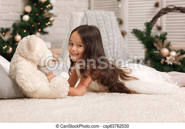 child girl playing with teddy bear near the Christmas tree - csp63762530