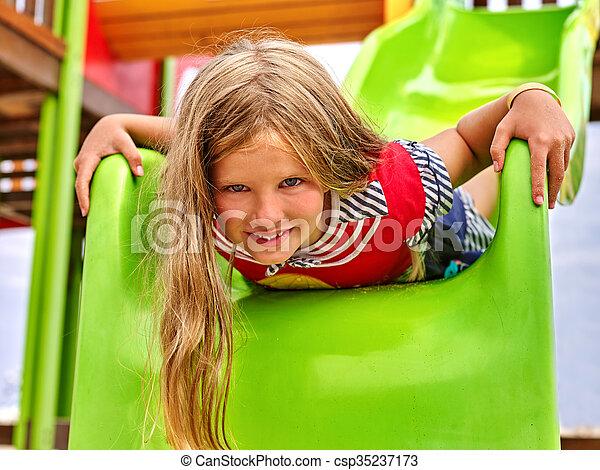 Child girl upside down on playground . - csp35237173