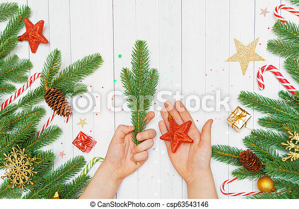 Child hand with on wooden background decorated christmas accessories. - csp63543146