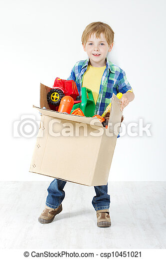 Child holding cardboard box packed with toys. Moving and growing concept - csp10451021