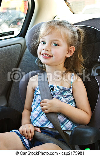 Child in car seat. Little girl in a car seat smiling at camera.