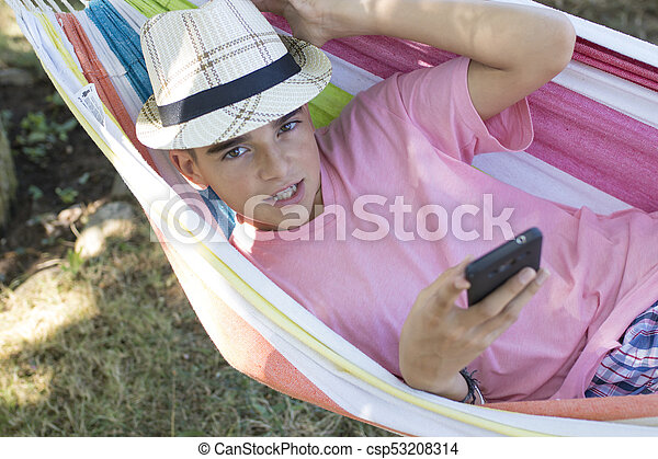 child in hammock with mobile phone - csp53208314