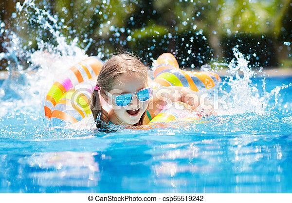 Child in swimming pool. Kids swim. Water play. - csp65519242