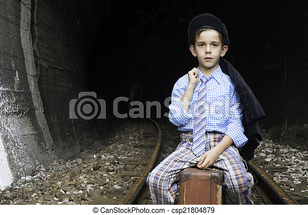 Child in vintage clothes sits on railway road - csp21804879