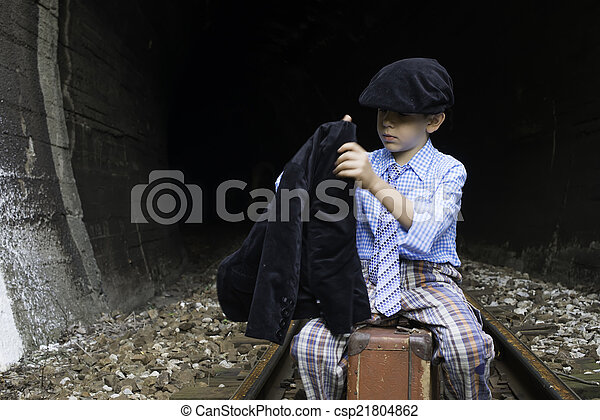 Child in vintage clothes sits on railway road - csp21804862