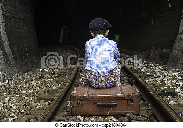 Child in vintage clothes sits on railway road - csp21804864