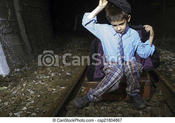 Child in vintage clothes sits on railway road - csp21804867