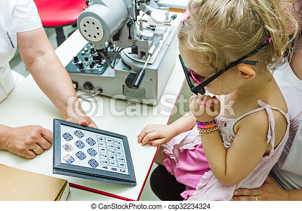 Child is at eye examination in clinic with special equipment