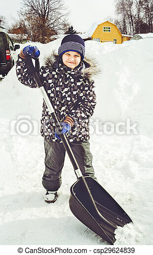 Child is shoveling snow in front of - csp29624839
