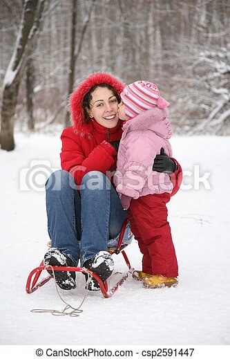 child kiss mother sits in sled in park at winter - csp2591447