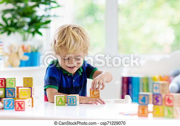 Child learning letters. Kid with wooden abc blocks - csp71229070