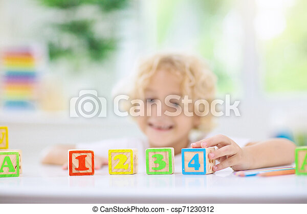 Child learning letters. Kid with wooden abc blocks - csp71230312