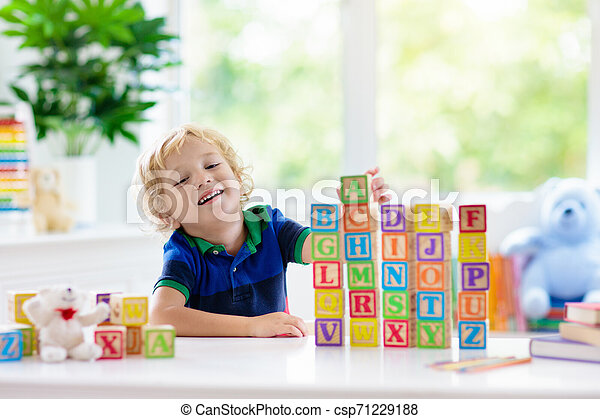 Child learning letters. Kid with wooden abc blocks - csp71229188