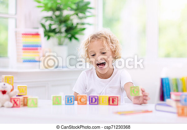 Child learning letters. Kid with wooden abc blocks - csp71230368