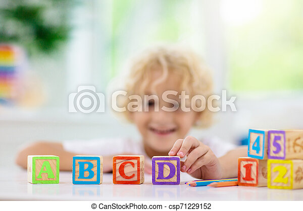 Child learning letters. Kid with wooden abc blocks - csp71229152