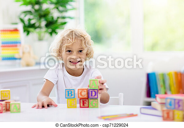 Child learning letters. Kid with wooden abc blocks - csp71229024