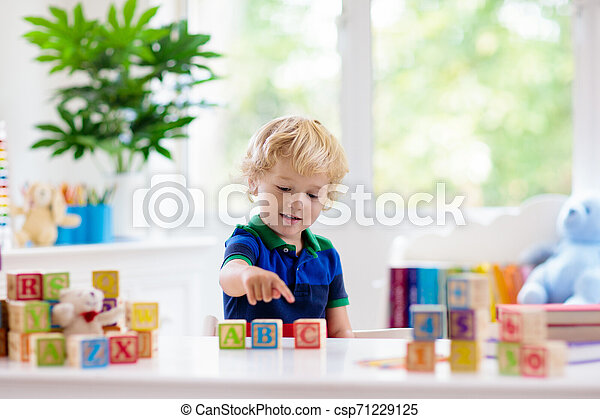 Child learning letters. Kid with wooden abc blocks - csp71229125