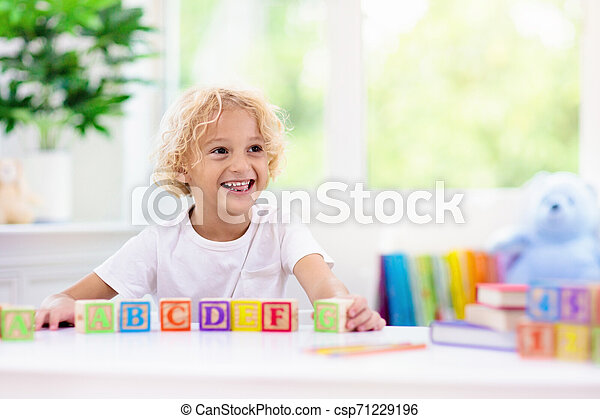 Child learning letters. Kid with wooden abc blocks - csp71229196
