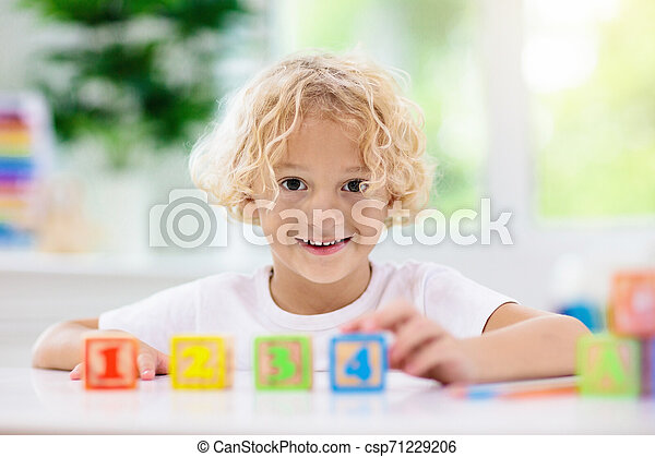 Child learning letters. Kid with wooden abc blocks - csp71229206