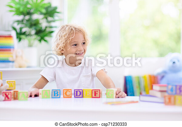 Child learning letters. Kid with wooden abc blocks - csp71230333