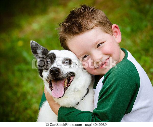 Child lovingly embraces his pet dog - csp14049989