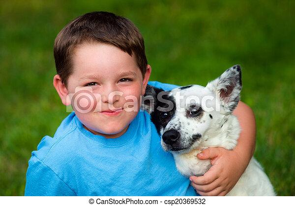 Child lovingly embraces his pet dog - csp20369532