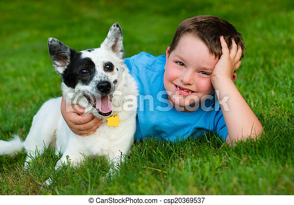 Child lovingly embraces his pet dog - csp20369537