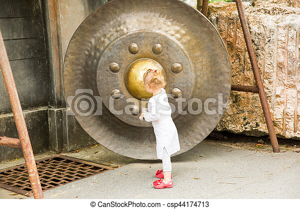 Child near Thai gong in Phuket. Tradition asian bell in Buddhism temple in Thailand. Famous Big bell wish near Gold Buddha - csp44174713
