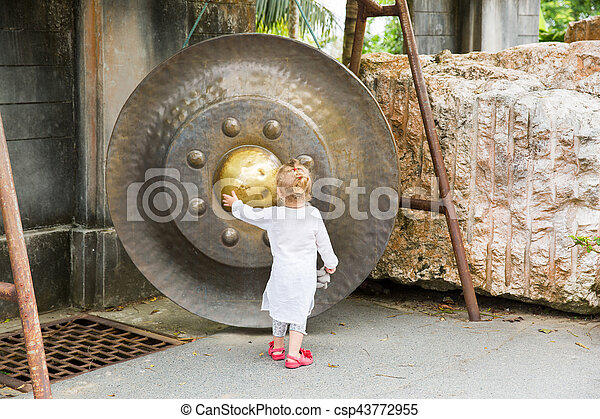 Child near Thai gong in Phuket. Tradition asian bell in Buddhism temple in Thailand. Famous Big bell wish near Gold Buddha - csp43772955