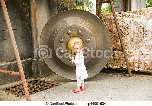 Child near Thai gong in Phuket. Tradition asian bell in Buddhism temple in Thailand. Famous Big bell wish near Gold Buddha - csp44001634