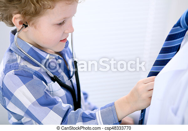 Child patient examining his doctor by stethoscope - csp48333770