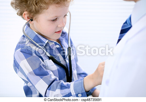 Child patient examining his doctor by stethoscope - csp48735691