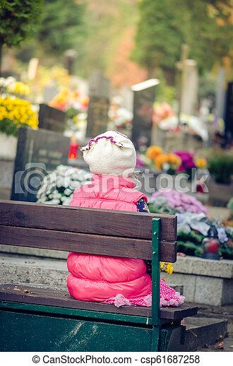 child praying in cemetery - csp61687258