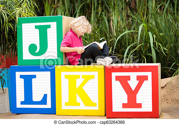 Child reading book. Kid learning letters. - csp63264366