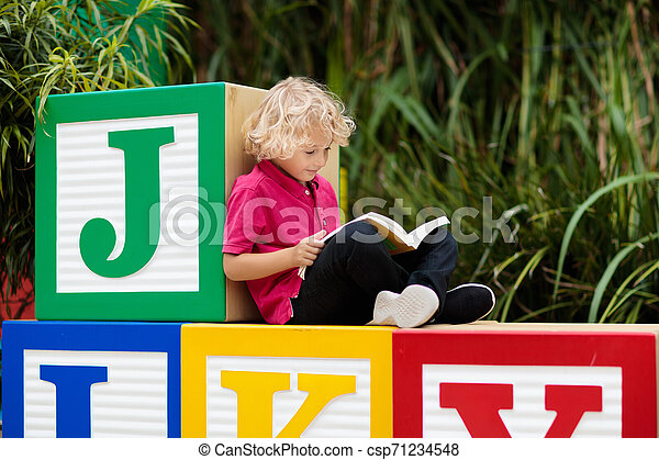 Child reading book. Kid learning letters. - csp71234548