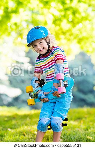 Child riding skateboard in summer park - csp55555131